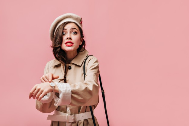 emotional-woman-beige-trench-coat-light-colored-hat-looks-into-camera-points-wrist-watch_197531-17637