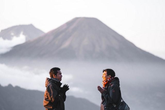 Muž a žena v zimnom oblečení stoja vonku v horách