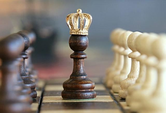 Hnedá šachová figúrka na šachovnici so zlatou korunou na hlave.jpg