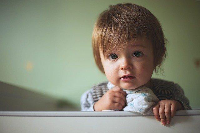 Dieťa s hnedými vlasmi pozerá cez zábradlie z postieľky.jpg