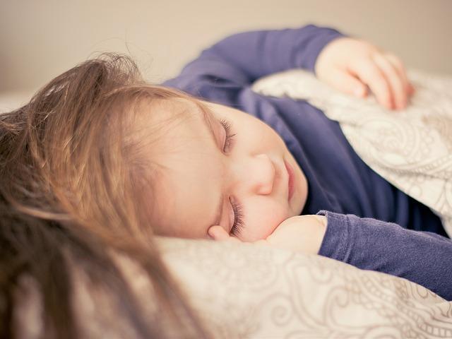 Dievča s dlhými hnedými vlasmi spí v posteli pod paplónom.jpg